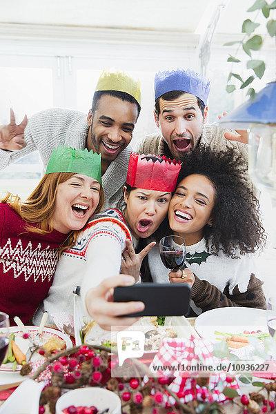 Dumme Freunde in Papierkronen  die beim Weihnachtsessen Selfie nehmen