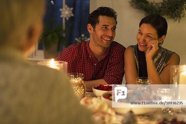 Lächelndes Paar beim Weihnachtsessen bei Kerzenschein