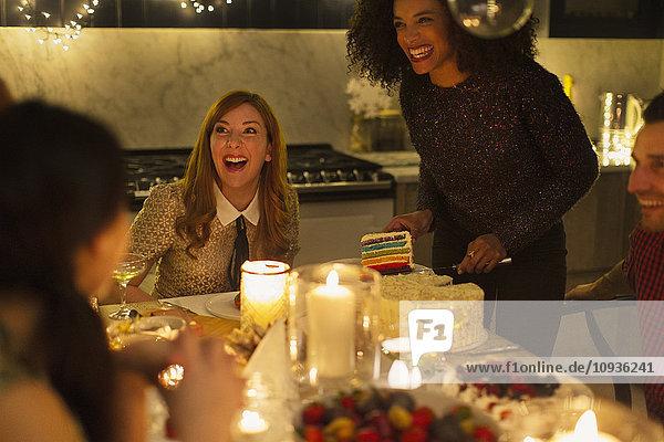 Lachende Freunde genießen Kuchen auf der Candlelight-Weihnachtsfeier