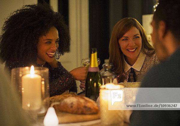Lächelnde Freunde trinken Champagner am Candlelight-Dinner-Tisch
