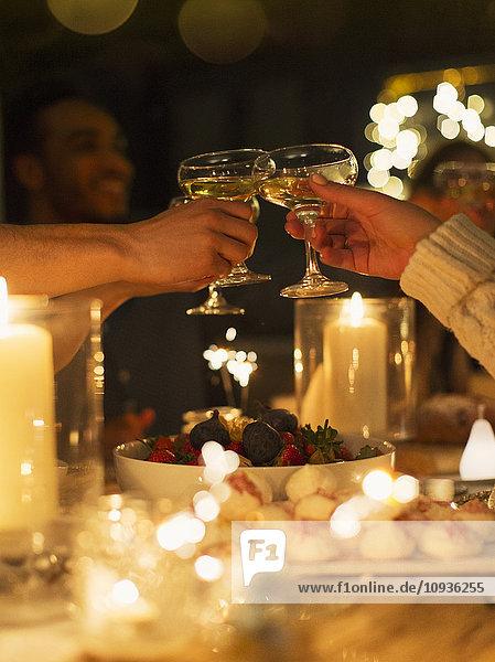Freunde rösten Champagnergläser über dem Tisch bei Kerzenschein.