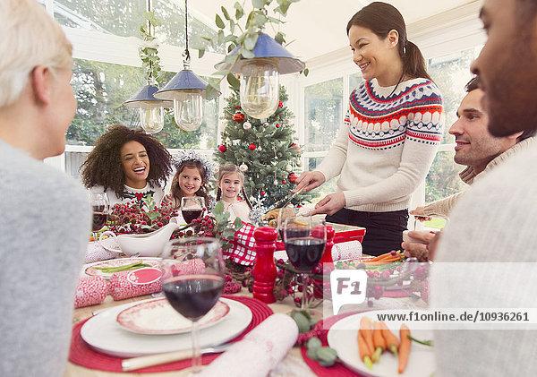 Frau serviert Truthahn am Weihnachtstisch
