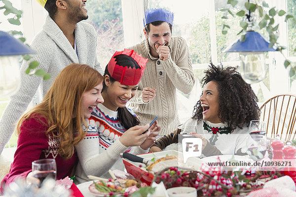 Lachende Freunde mit Papierkronen beim Weihnachtsessen