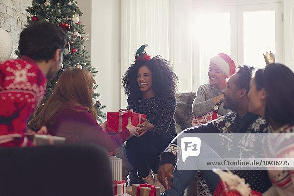 Lächelnde Freunde beim Austausch von Weihnachtsgeschenken im Wohnzimmer