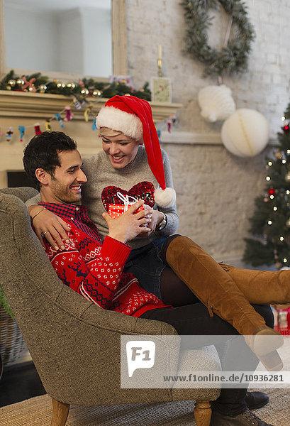 Liebespaar beim Öffnen von Weihnachtsgeschenken im Wohnzimmer