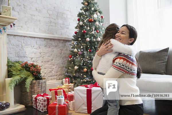 Mutter und Tochter beim Umarmen am Weihnachtsbaum und Geschenke im Wohnzimmer