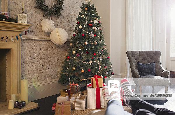 Entspanntes Paar mit Socken und Füßen in der Nähe des Weihnachtsbaums im Wohnzimmer