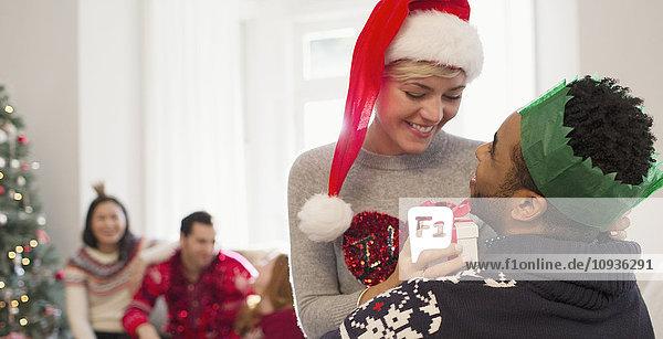 Liebespaar mit Weihnachtsgeschenk im Wohnzimmer