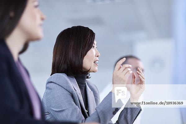 Geschäftsfrau gestikuliert und erklärt im Meeting
