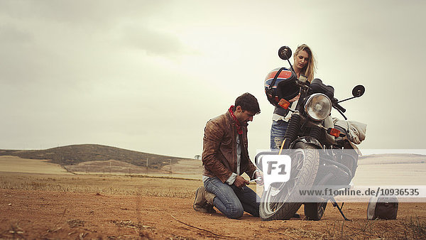 Young couple repairing motorcycle in remote countryside field