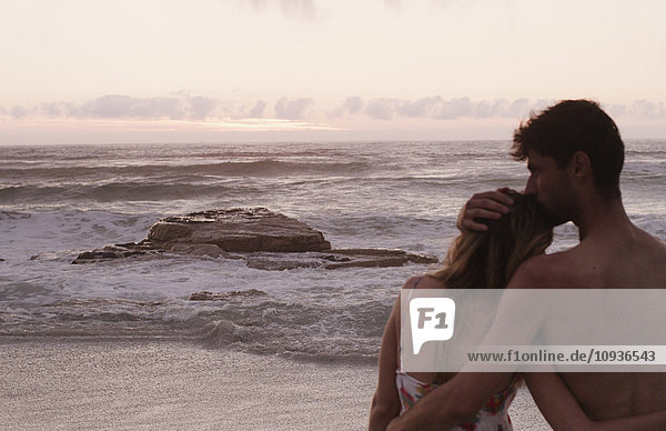 Affectionate young couple on calm beach