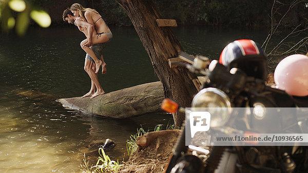 Young couple piggybacking at lakeside behind motorcycle