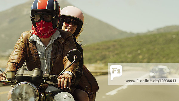 Young couple riding motorcycle on sunny road