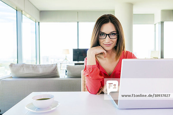 Woman in apartment using laptop computer