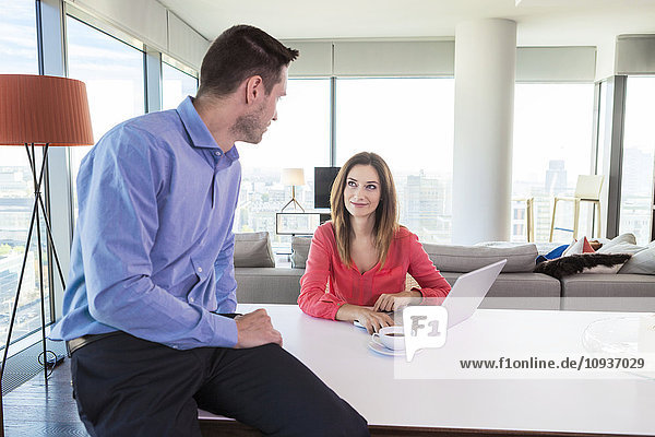 Couple in apartment using laptop