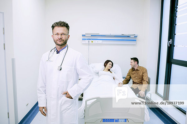 Doctor with patient in sick room of hospital