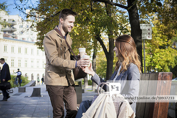 Mid adult couple in park having a cup of coffee
