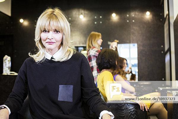 Portrait of female hairstylist in hair salon