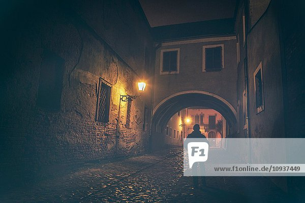 Lonely man standing in Old Town of Osijek at night