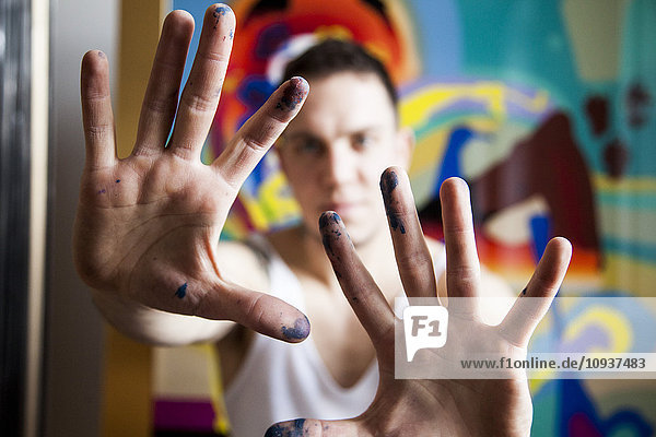 Male painter in artist studio showing his dirty hands
