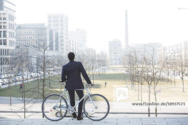 Businessman with bicycle taking a break in city