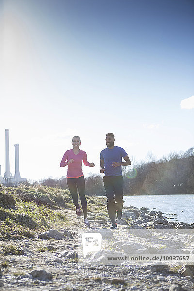 Young couple jogging by the riverside