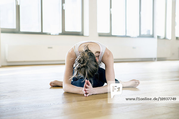 Woman sits in yoga pose bending over