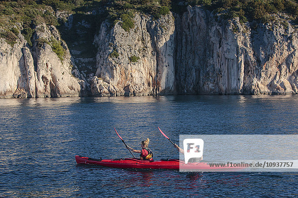 Two people kayaking next to rock formation