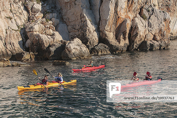 Group of people kayaking next to rock formation