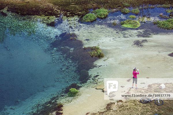 Female mountain biker next to blue lake drinking water