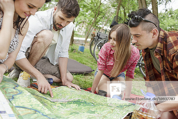 Group of friends reading map at campsite