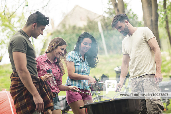 Group of friends having barbecue at campsite