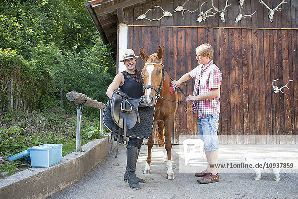 Couple on ranch saddling horse