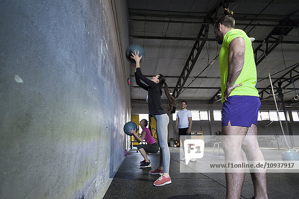 Athletes exercising with medicine ball in gym