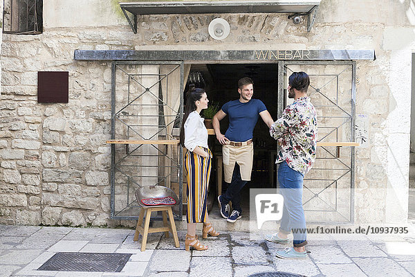Owner of wine bar talking to friends outside