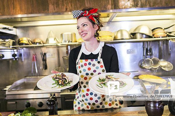 Female chef in restaurant serving fresh calamari dish