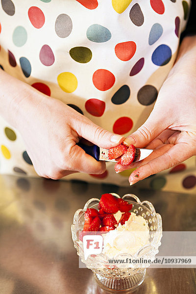 Person cutting strawberries to prepare a dessert