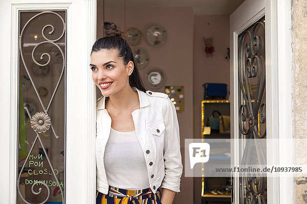 Portrait of young woman in door of restaurant