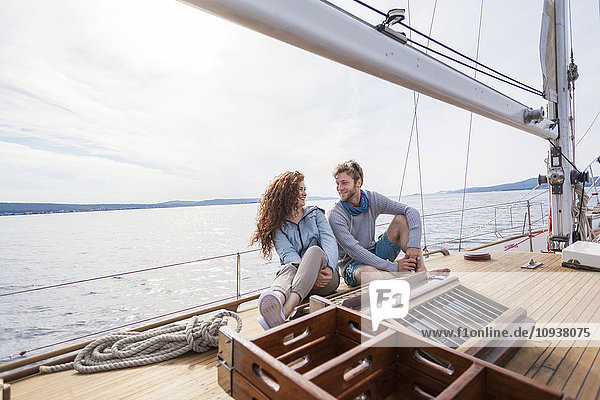 Young couple relaxing on boat deck of yacht
