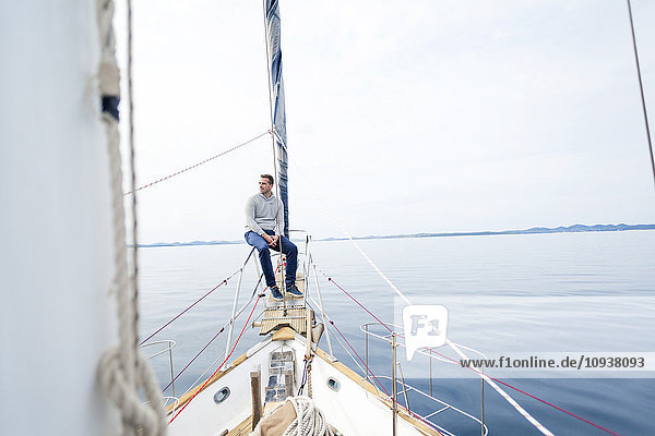Man sits on bow of yacht day dreaming