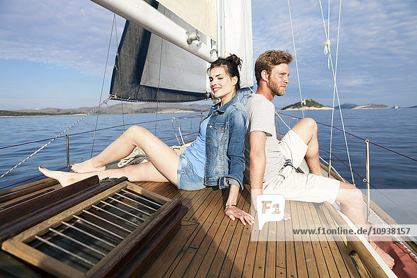 Young couple sitting back to back on sailboat