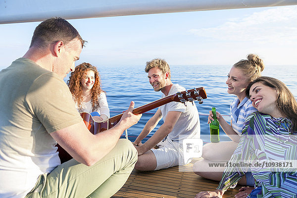 Young man playing guitar on sailboat with friends listening