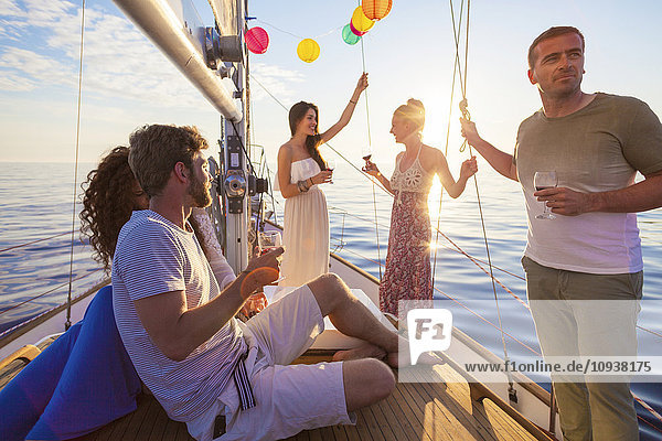 Friends celebrating with wine on sailboat
