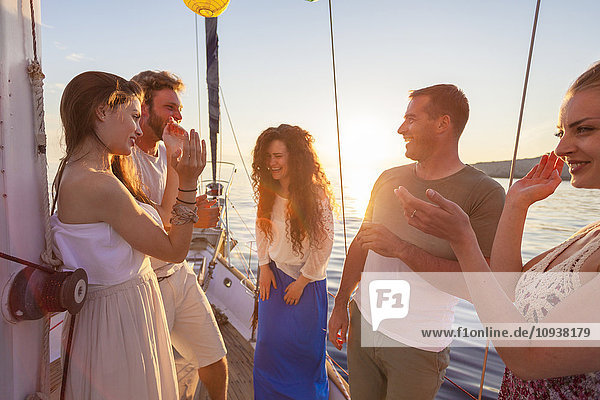 Friends celebrating and laughing on sailboat