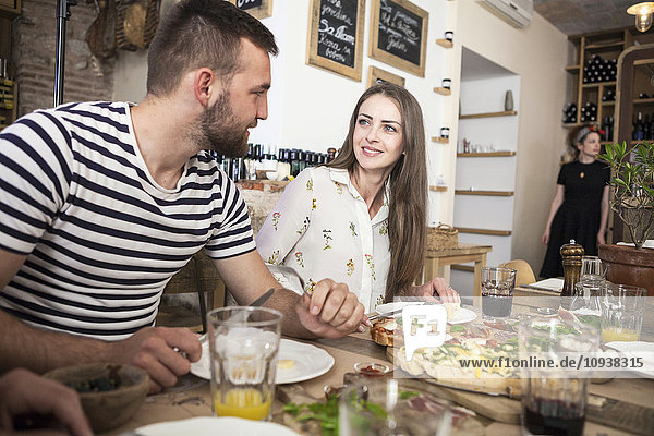 Young couple enjoying lunch at restaurant