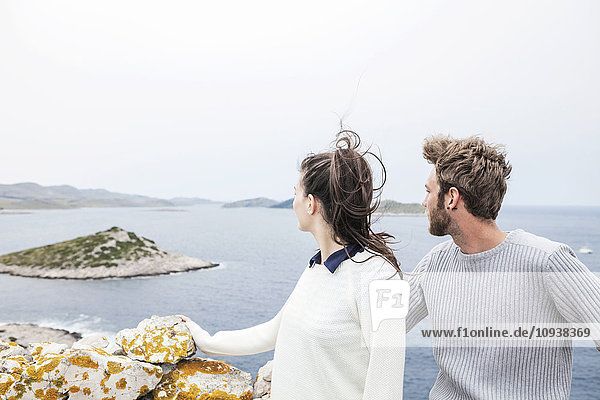 Young couple on a cliff looking out to sea