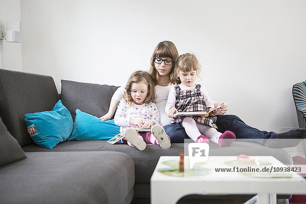 Mother and daughters on sofa looking at picture book
