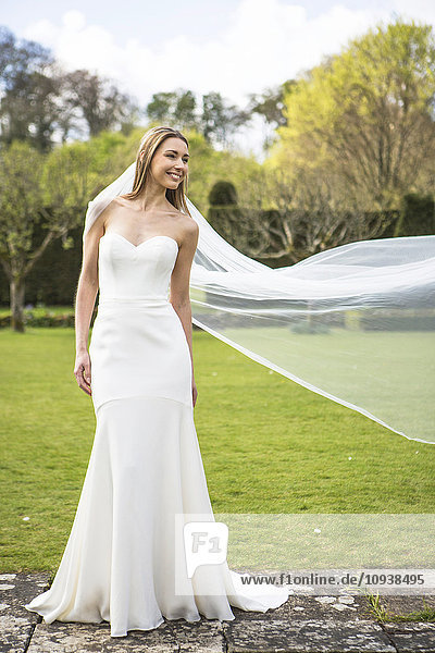 Bride showing off wedding dress outdoors