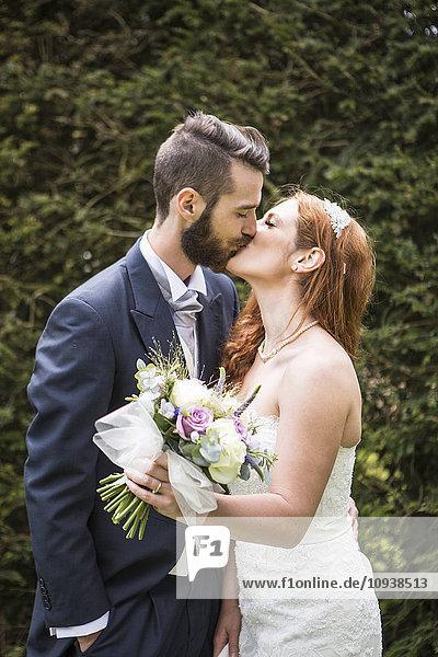 Bridegroom kissing bride with bouquet