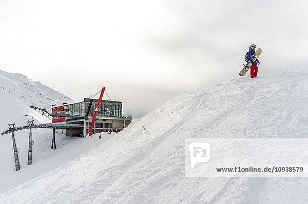 Snowboarder carrying snowboard near ski lift